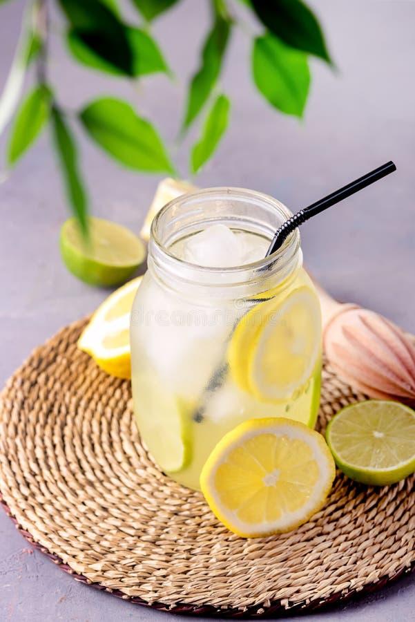 Detox-Wasser mit Zitrone amd Kalk und geschmackvolles Sommer-Limonaden-Getränk mit Eis-Würfel Detox-gesunder Getränk-Vertikale zu stockfotos