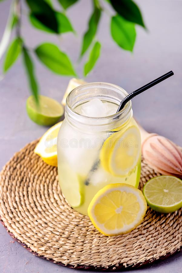 Detox Water With Lemon amd Lime and Ice Tasty Summer Lemonade Drink with Ice Cube Detox Healthy Drink Vertical Infused Water.  stock photos