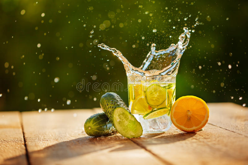 Detox water with lemon and cucumbers with splash on wooden table. And green nature background stock photo