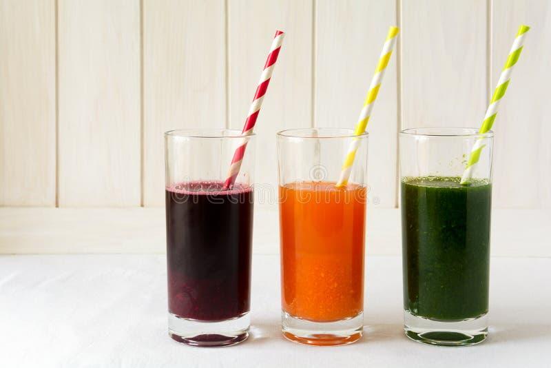 Detoxdrinkar i exponeringsglas: nya smoothies från grönsaker: beta, morot, spenat, gurka och äpple royaltyfri bild