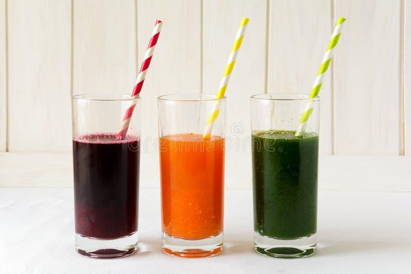 Detoxdrinkar i exponeringsglas: nya smoothies från grönsaker: beta, morot, spenat, gurka och äpple arkivbild