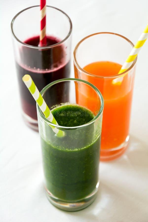 Detoxdrinkar i exponeringsglas: nya smoothies från grönsaker: beta, morot, spenat, gurka och äpple arkivfoto