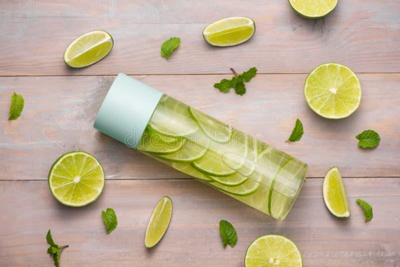 Detoxen ingav vatten med limefrukt och mintkaramellen i sportflaska, med sl royaltyfria foton