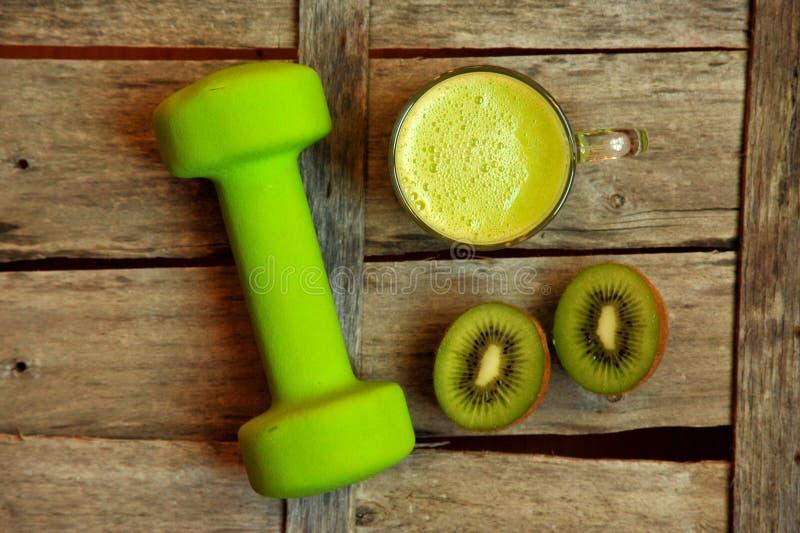 Detoxlebensmittel mit Kiwi smootie und einem grünen anhebenden Gewicht lizenzfreies stockfoto