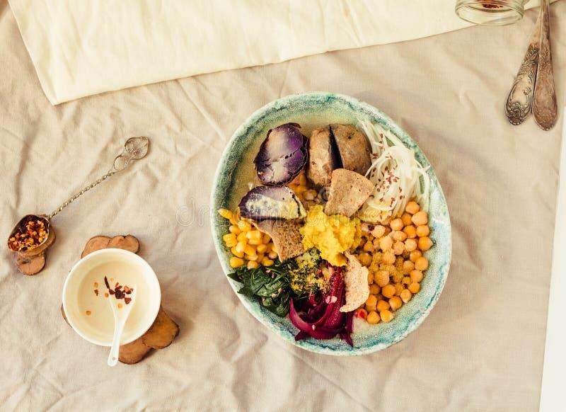 Detoxlunch med en purpurfärgad potatis, kokta spenat och en hummus med havresmällare arkivbild