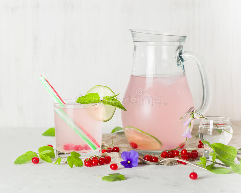 Detoxvatten i en glass tillbringare och ett exponeringsglas Bär och limefrukt, rött och grönt ny leavesmint kopiera avstånd fotografering för bildbyråer