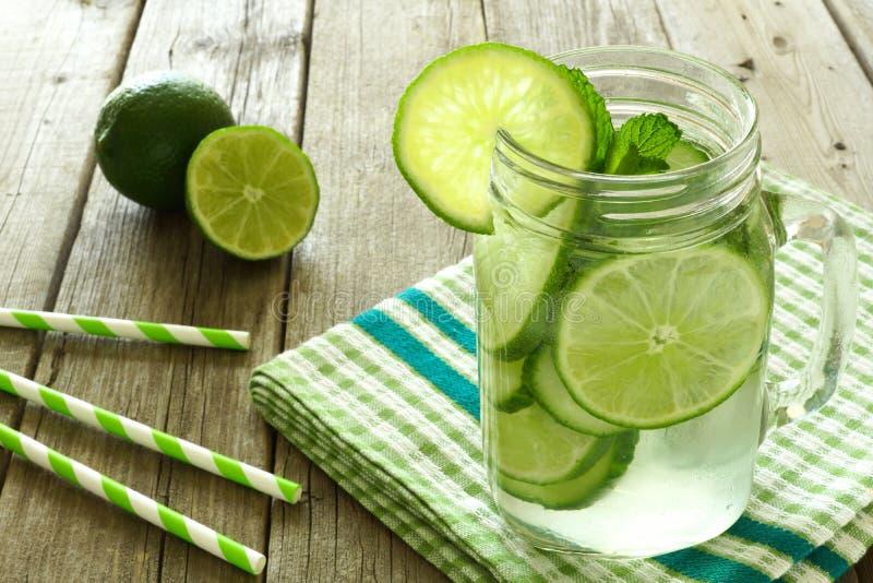 Detoxvatten med limefrukt och gurkor i krus mot trä royaltyfri fotografi