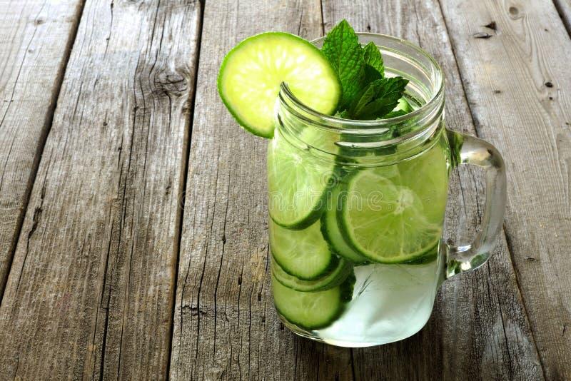 Detoxwater met kalk en komkommers op oud hout royalty-vrije stock foto's