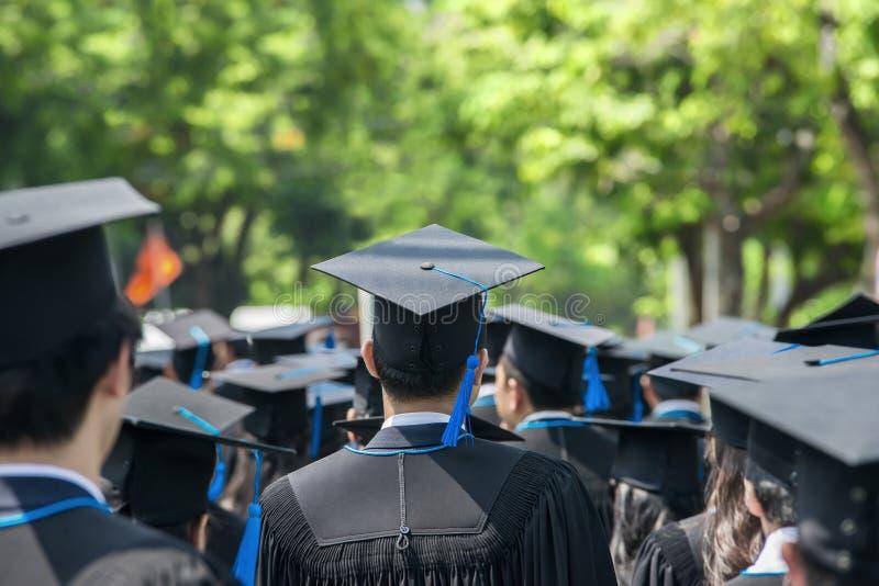 Detrás de graduados durante el comienzo en la universidad imágenes de archivo libres de regalías