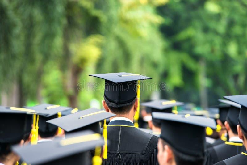 Detrás de graduados durante el comienzo en la universidad fotos de archivo libres de regalías