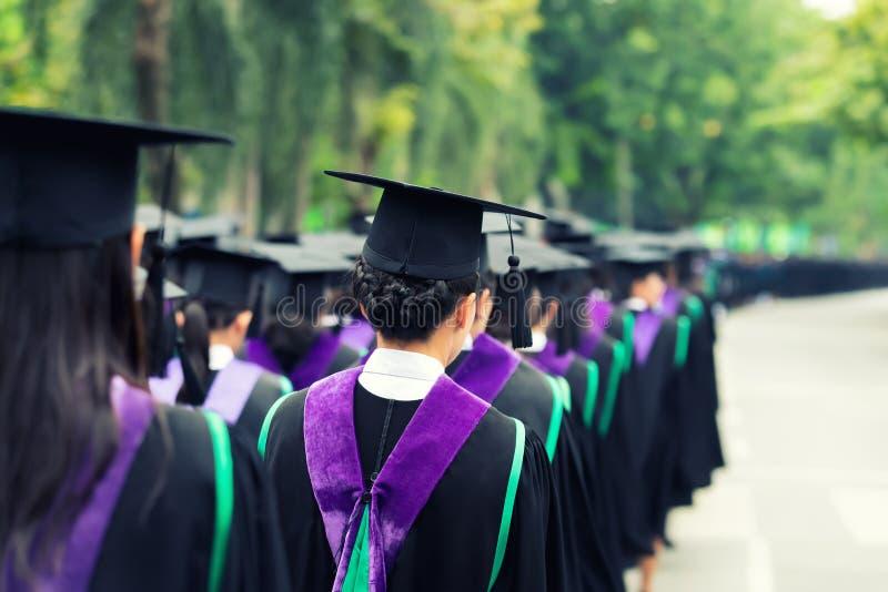 Detrás de graduados durante el comienzo en la universidad Ciérrese para arriba en imagen de archivo libre de regalías