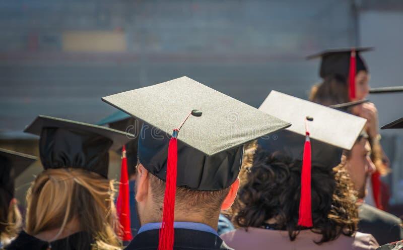 Detrás de graduados durante el comienzo en la universidad, cierre para arriba en el casquillo graduado Ceremonia de graduación foto de archivo
