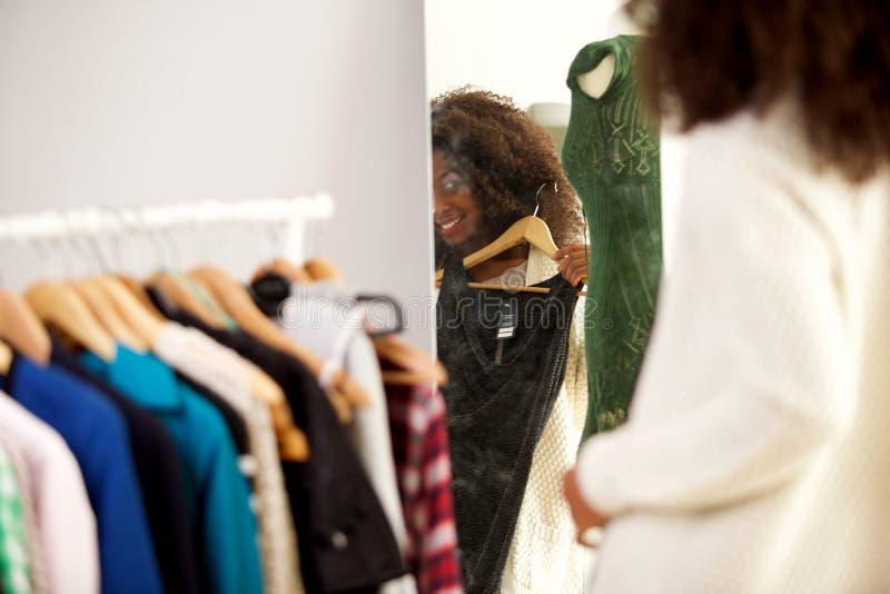 Detrás de la mujer africana joven sonriente que mira en un espejo e intentos un nuevo vestido foto de archivo