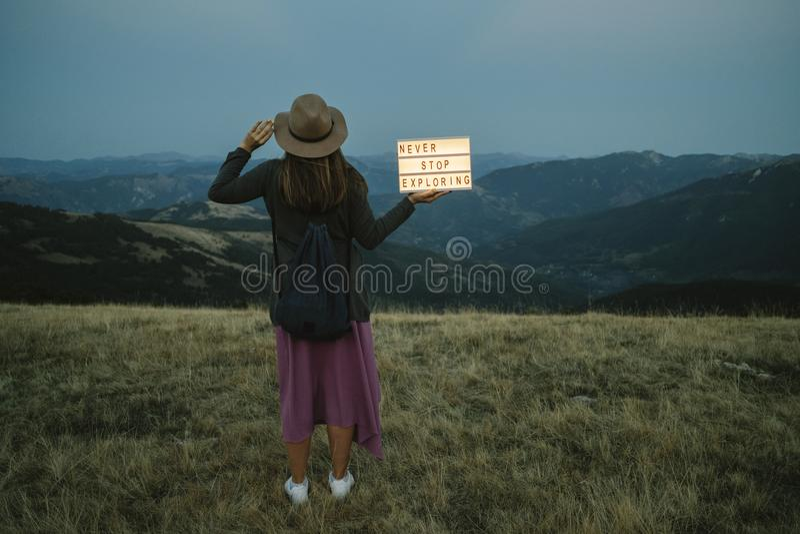 Detrás de la mujer con la caja con el texto nunca pare el explorar contra t foto de archivo