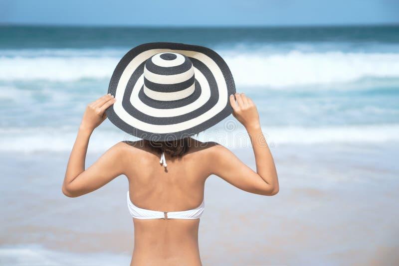 Detrás de la mujer joven en el bikini que se coloca en la playa, mujer atractiva hermosa joven en el traje de baño del bikini, is foto de archivo libre de regalías