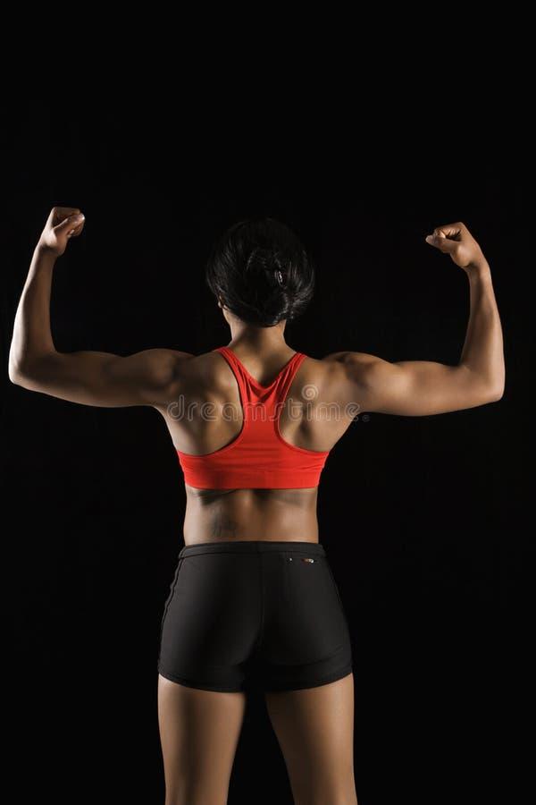 Detrás de la mujer muscular. foto de archivo libre de regalías