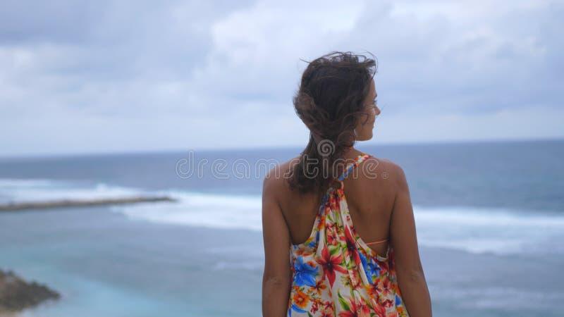 Detrás de la opinión la mujer morena joven pensativa con el pelo largo que lleva el vestido largo que defiende en una roca el océ foto de archivo libre de regalías