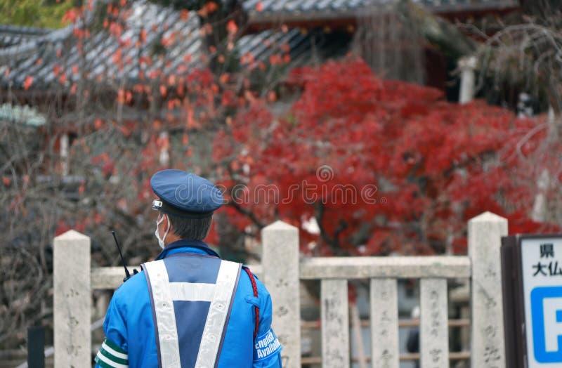 Detrás de la policía de tráfico japonesa en deberes de ejecución uniformes del azul en la calle con el árbol rojo del fondo en ot imagen de archivo libre de regalías