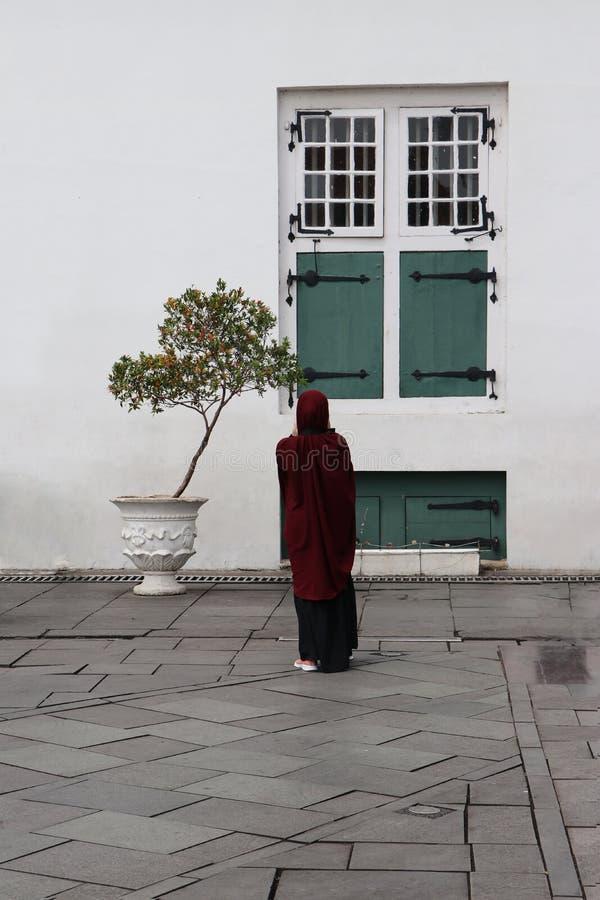 Detrás de la situación indonesia de la mujer musulmán con la ventana verde fotografía de archivo libre de regalías
