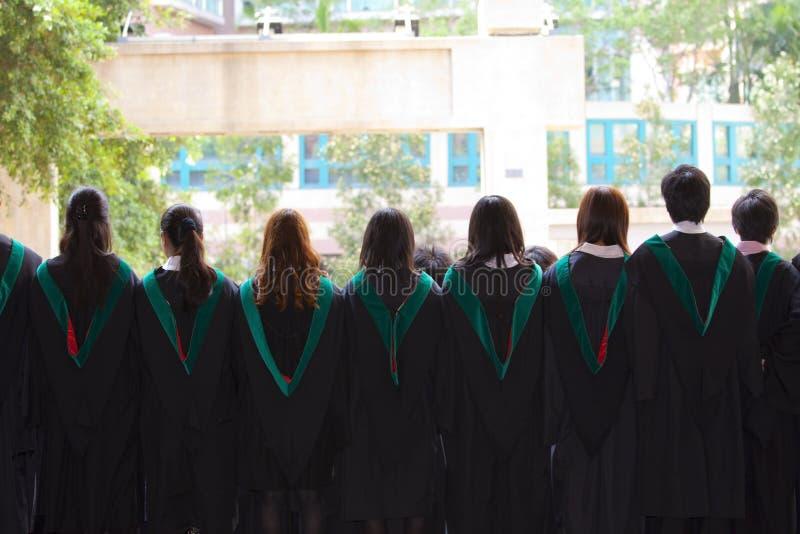 Detrás de la universidad gradúa con sus vestidos fotografía de archivo