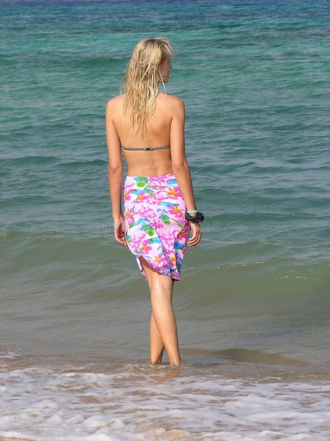 Detrás de muchacha rubia en la playa foto de archivo