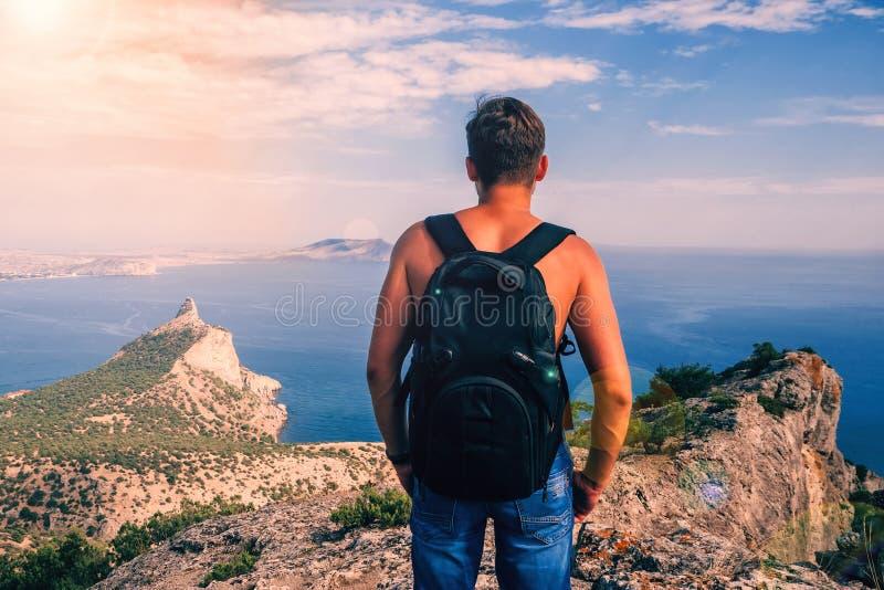 Detrás de un hombre con una mochila encima de las montañas contra el cielo y el mar imagen de archivo libre de regalías