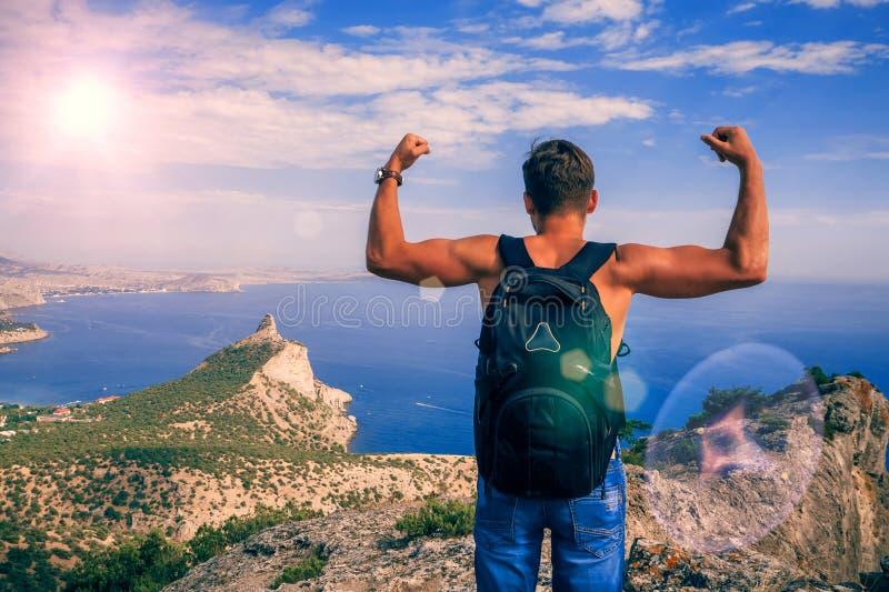 Detrás de un hombre con una mochila encima de las montañas con las manos fuertes aumentadas para arriba fotos de archivo