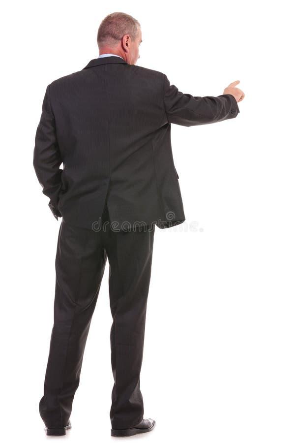 Detrás de un hombre de negocios que empuja un botón fotos de archivo libres de regalías