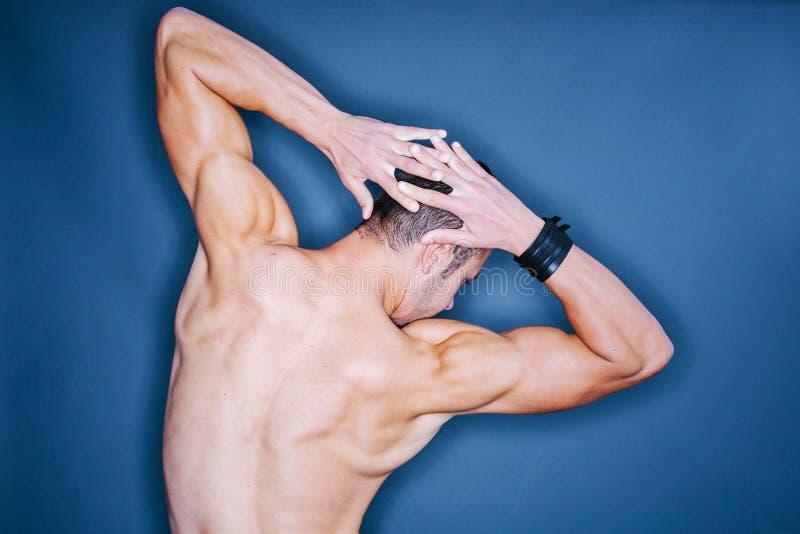 Detrás de un hombre muscular imagenes de archivo