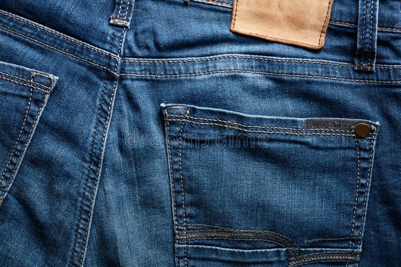 Detrás de una mezclilla azul del color del añil y de su bolsillo fotos de archivo