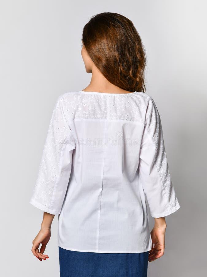 Detr?s de una muchacha morena joven con el pelo largo en una blusa blanca y una falda azul En un fondo ligero fotografía de archivo libre de regalías
