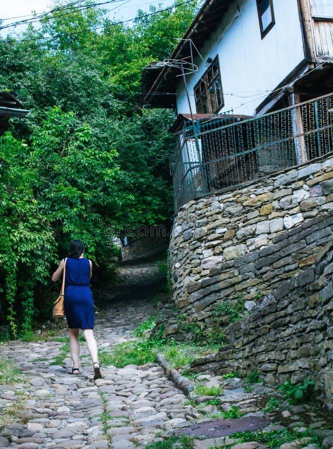 Detrás de una muchacha que camina a través de las calles antiguas de un pueblo tradicional de Bulgaria en un vestido azul foto de archivo libre de regalías