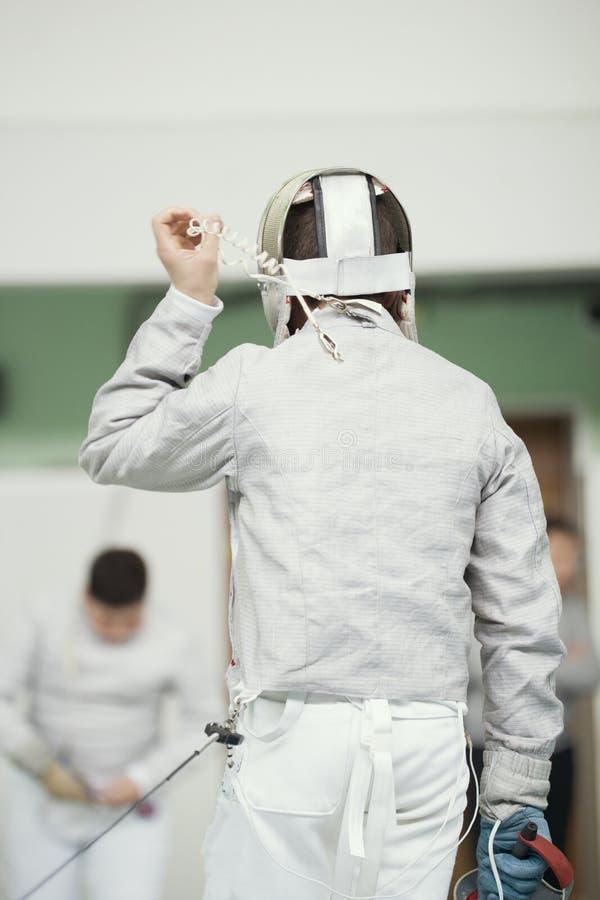 Detrás del cercador joven en el traje blanco y la máscara protectora imagen de archivo