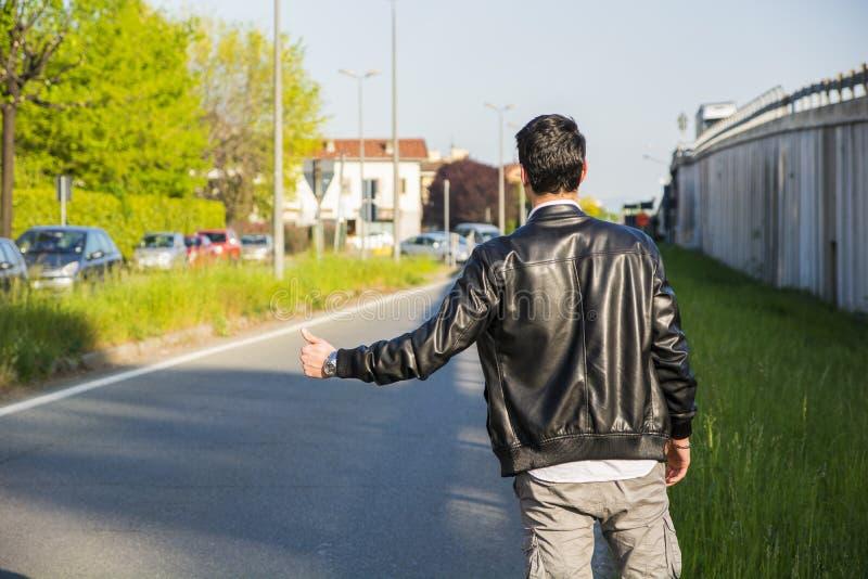 Detrás del hombre joven, autostopista que espera en el borde de la carretera fotografía de archivo libre de regalías
