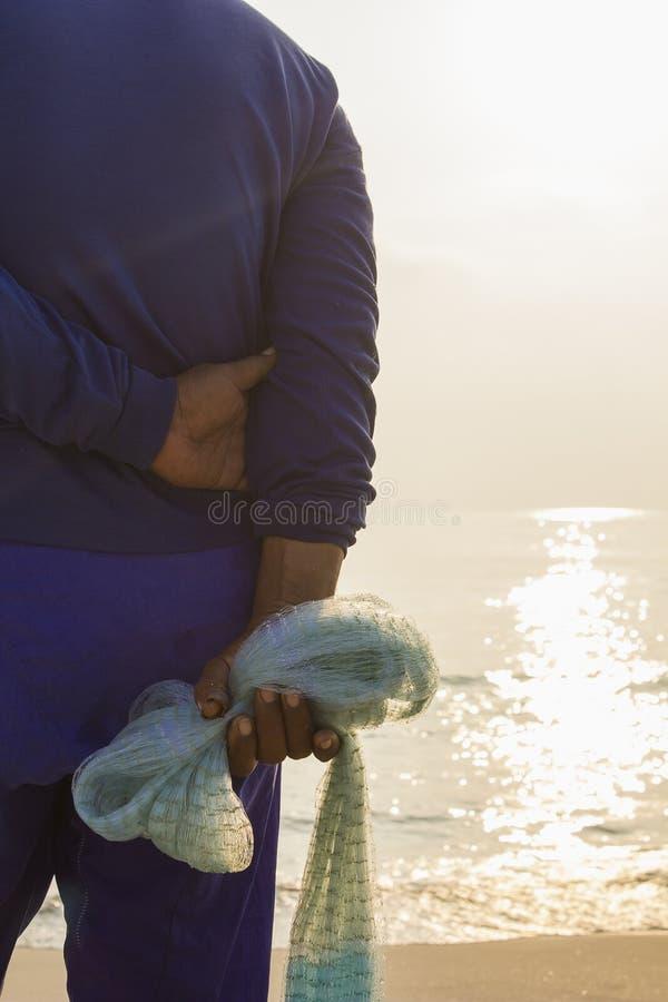 Detrás del pescador que sostiene la red imagen de archivo libre de regalías
