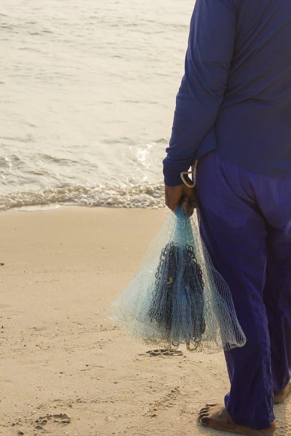 Detrás del pescador que sostiene la red fotografía de archivo