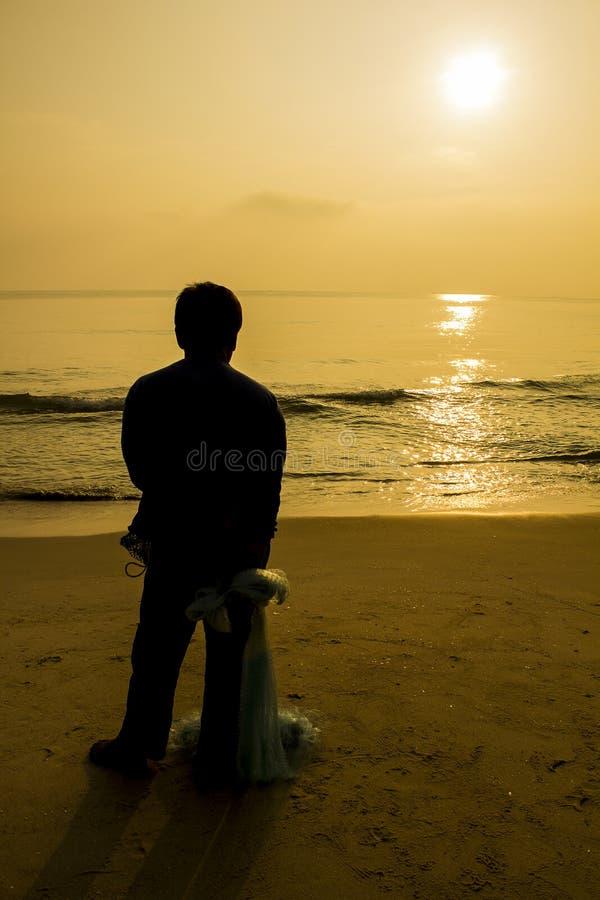 Detrás del pescador que sostiene la red; estilo de la silueta foto de archivo libre de regalías