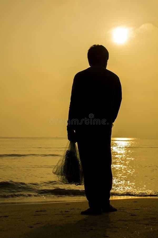 Detrás del pescador que sostiene la red; estilo de la silueta imagen de archivo