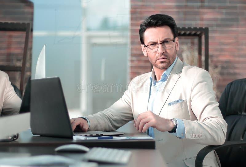 Detrás del vidrio un hombre de negocios serio que usa un ordenador portátil imágenes de archivo libres de regalías