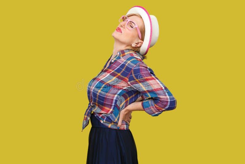 Detrás, dolor de la espina dorsal o del riñón Retrato de la vista lateral del perfil de la mujer madura elegante moderna en estil fotografía de archivo