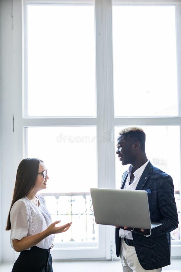 Detta är det. 指向膝上型计算机的俏丽的年轻亚裔女商人,当站立在她愉快的非洲的商人附近在前面时 库存照片