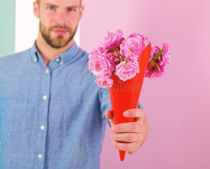 Detta är för dig som är macho, ger blommor som den romantiska gåvan För hållbukett för pojkvän säkra blommor Grabben kommer med r fotografering för bildbyråer