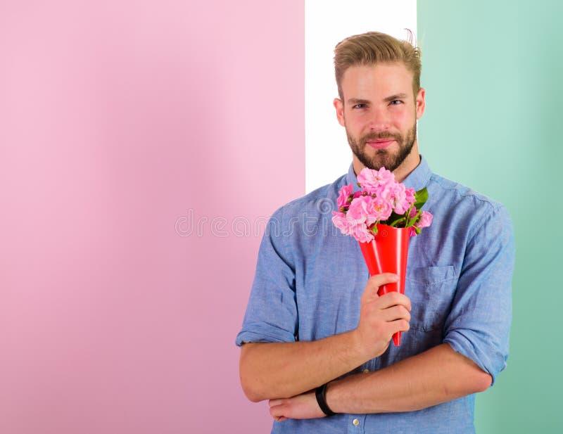 Detta är för som dig, kommer med mannen som är klar för romantiskt datum, buketten rosa blommor Macho ger blommor som den romanti royaltyfri foto
