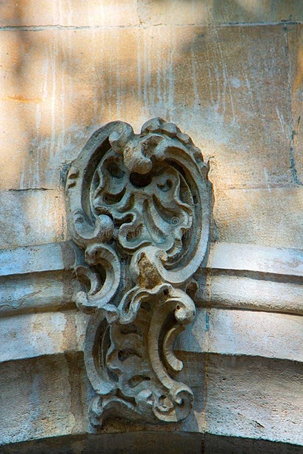 Dettagli architettonici su costruzione, pietra scolpenti, arricciamenti estetici fotografia stock