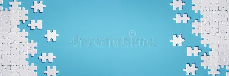Dettagli bianchi del puzzle su fondo blu fotografie stock