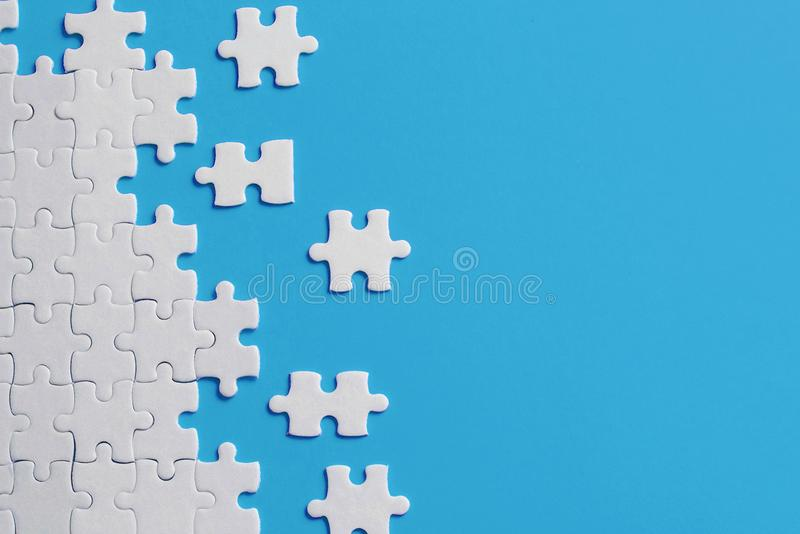 Dettagli bianchi del puzzle su fondo blu fotografia stock