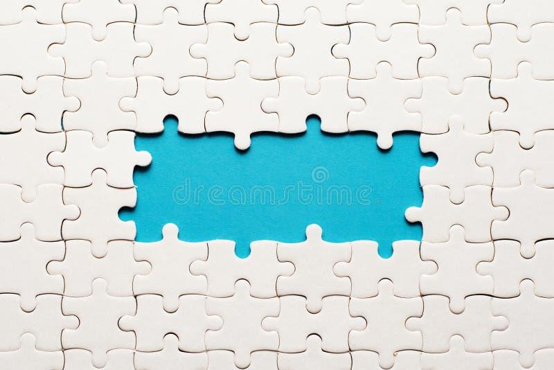 Dettagli bianchi del puzzle su fondo blu e del posto per l'iscrizione fotografia stock libera da diritti