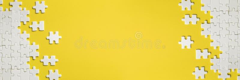 Dettagli bianchi del puzzle su fondo giallo fotografia stock libera da diritti