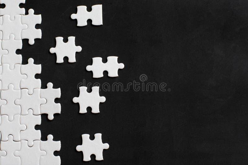 Dettagli bianchi del puzzle su fondo nero Con lo spazio della copia fotografia stock libera da diritti
