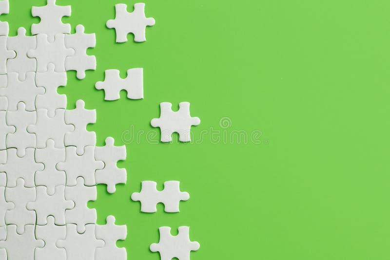 Dettagli bianchi del puzzle su fondo verde fotografie stock libere da diritti